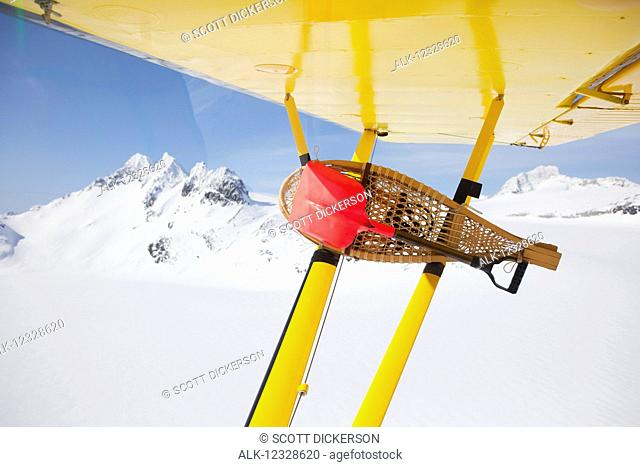 Snowshoes and small shovel attached to the wing of a Piper Super Cub while in flight, Kenai Mountains, Kachemak Bay State Park, South-central Alaska; Alaska