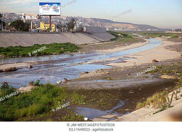 San Ysidro, California - The polluted Tijuana River as it enters the United States from Mexico  The yellow line on the far bank is the boundary between the two...