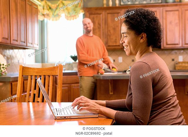 Mid adult woman using laptop while mid adult man cutting fruits