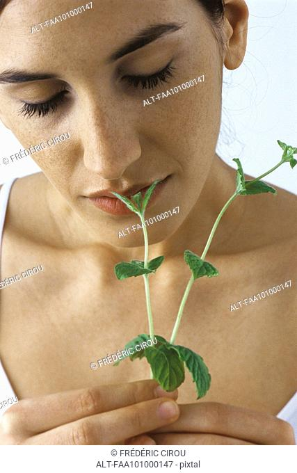 Young woman smelling fresh mint, eyes closed