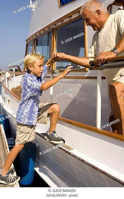 Grandfather helping grandson onto boat