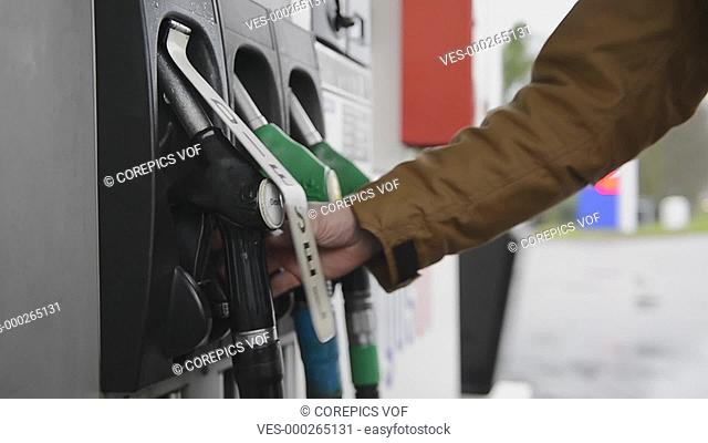 Man ring the nozzle from a diesel pump