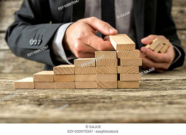 Front closeup view of businessman constructing steps of wooden pegs with focus to the peg in his hand, shallow dof