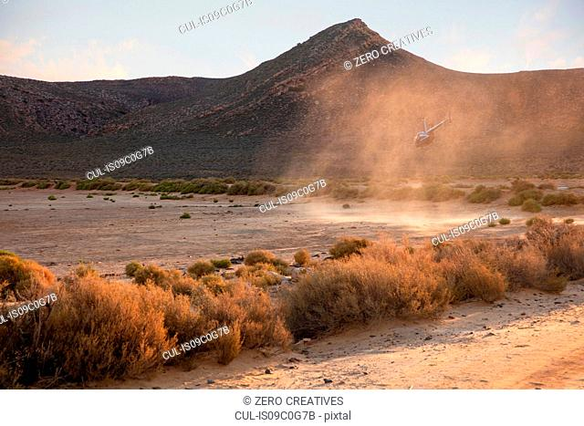 Helicopter landing in dusty rural landscape, Cape Town, Western Cape, South Africa