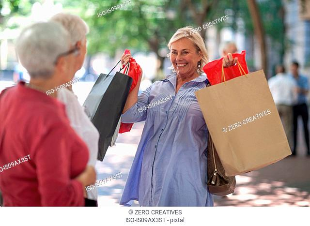 Senior and mature women holding up shopping bags in city