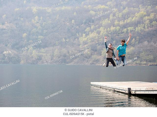 Young couple jumping mid air on pier at Lake Mergozzo, Verbania, Piemonte, Italy