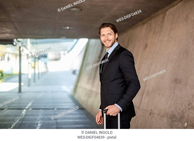 Smiling businessman with rolling suitcase standing in underpass