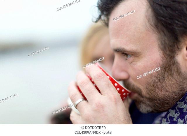 Couple on beach, man drinking hot drink