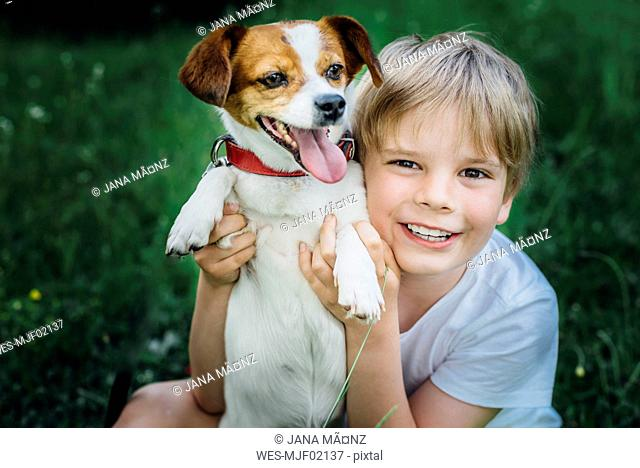 Portrait of happy little boy with his dog on meadow in the garden