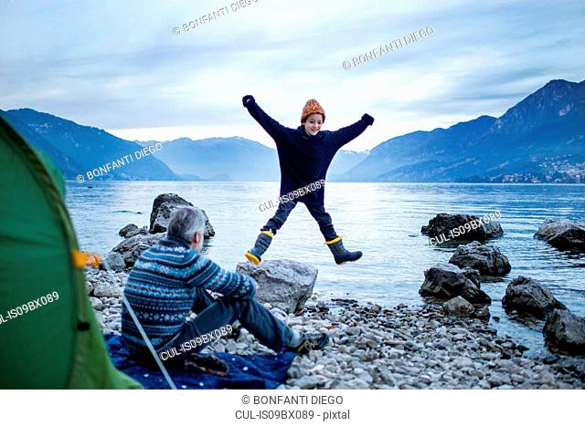 Father watching son doing star jump by lakeside, Onno, Lombardy, Italy