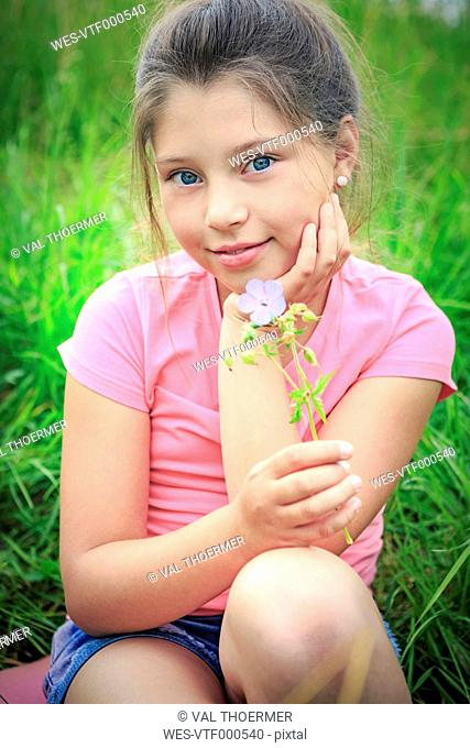 Portrait of smiling girl with flower sitting on a meadow