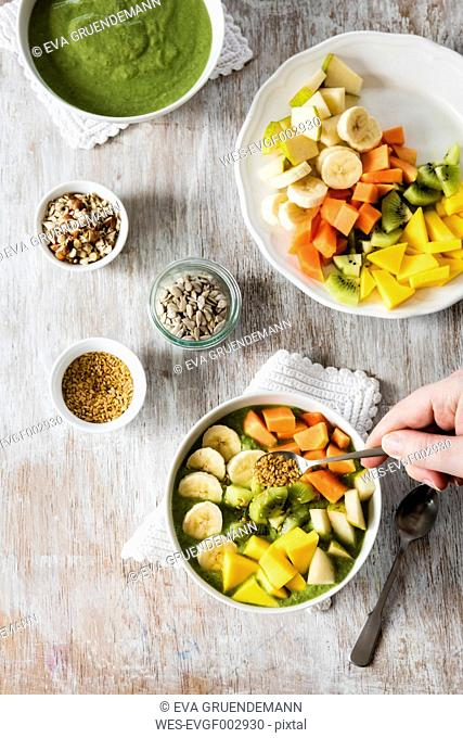 Smoothie bowl with different fruits, mango, papaya, kiwi, banana and pear and toppings, lineseeds, sunflower-seeds and nuts