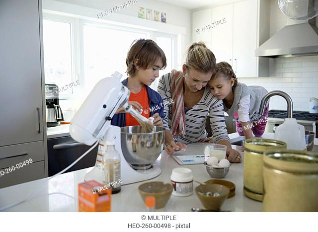 Mother and children baking with digital tablet kitchen