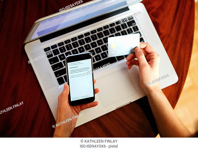 Overhead view of woman with laptop holding credit card and smartphone