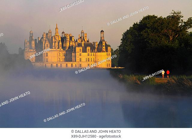 France, Loire Valley, Loir-et-Cher, Chambord, Château de Chambord, Men Jogging in the Park in early morning fog