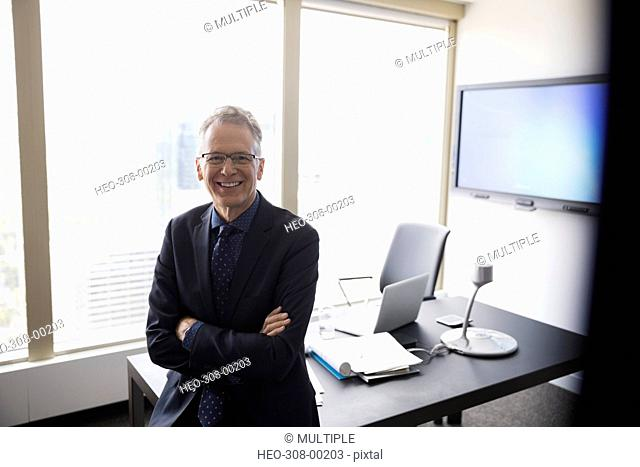 Portrait smiling businessman leaning on office desk