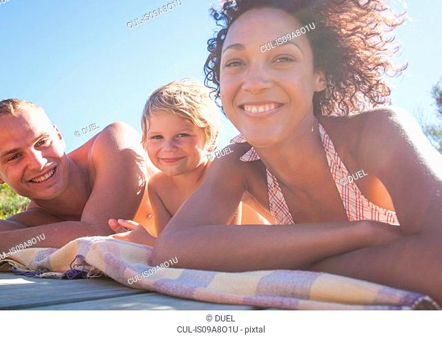 Man, woman and boy lying on their fronts sunbathing