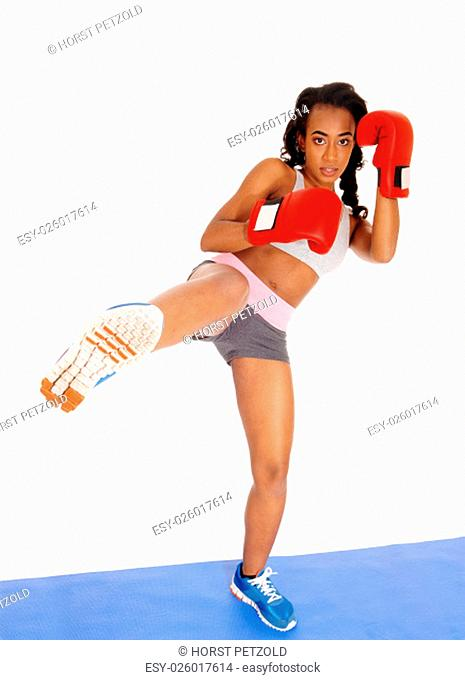 A slim African American girl standing on a blue mat during boxing exercise.with one leg up and red gloves, isolated for white background.