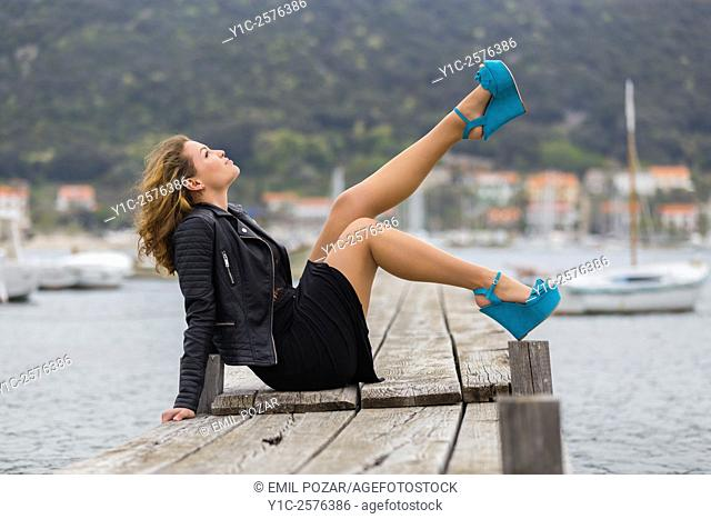 Pretty young lady posing on wooden quay