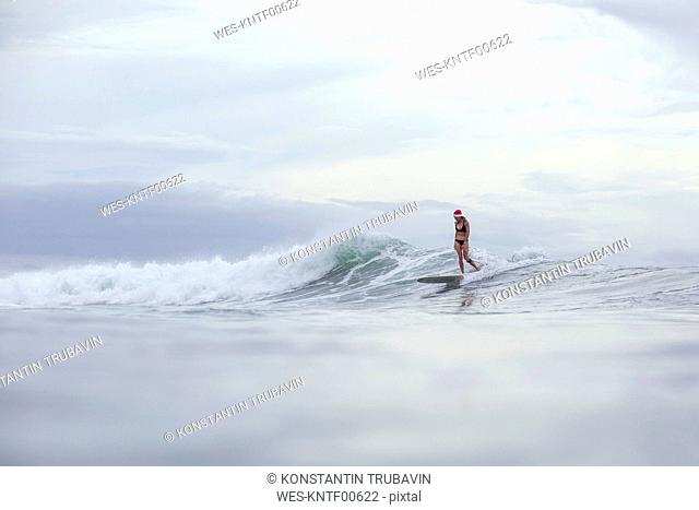 Indonesia, Bali, woman wearing Santa hat surfing on a wave