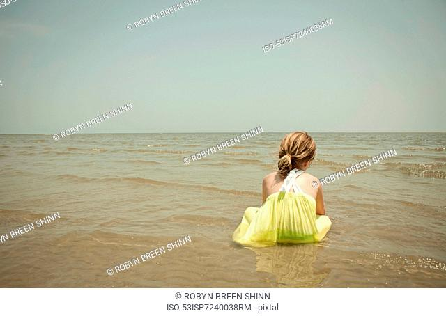 Girl playing in waves on beach