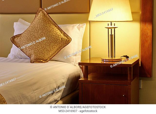A luxury bed with decorated pillow beside a besdide lamp