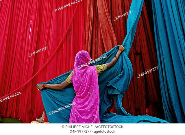 India, Rajasthan, Sari Factory, Textile are dried in the open air. Collecting of dry textile are folded by women and children