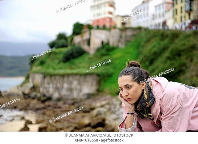 small town on top of a hill and a beautiful young woman reclining facing the beach