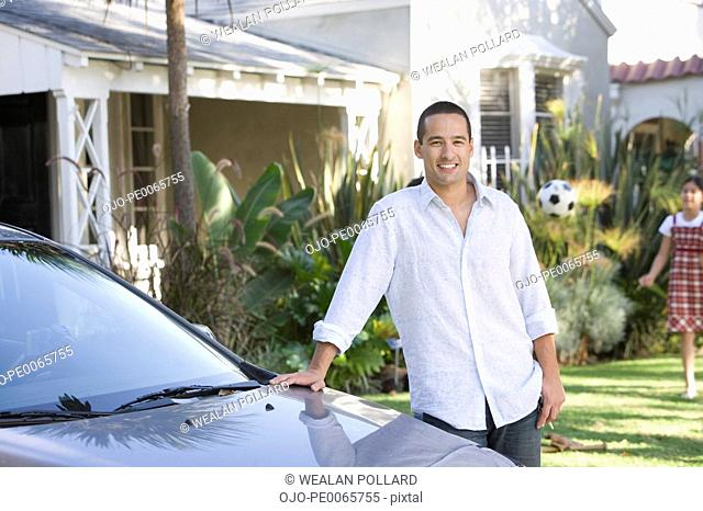 Father posing by car in driveway