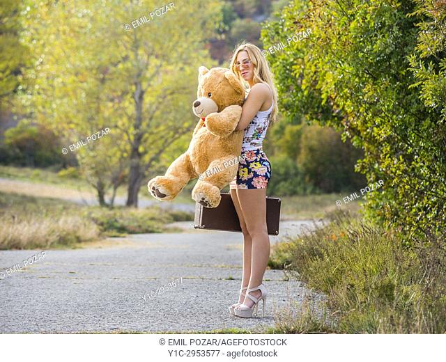 Teen girl standing waiting on country-road for somebody big teddy-bear in hand