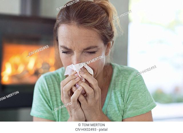 Woman with tissue blowing nose