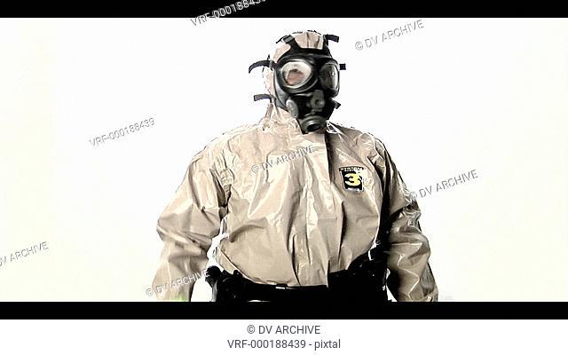 A man in a hazmat suit speaks into a walkie-talkie