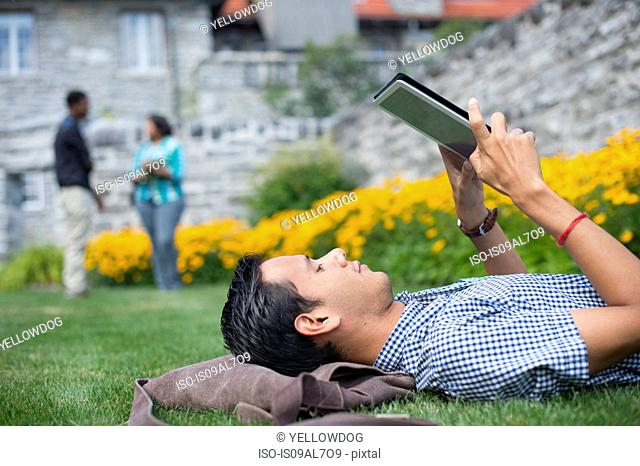Male student lying on grass using digital tablet
