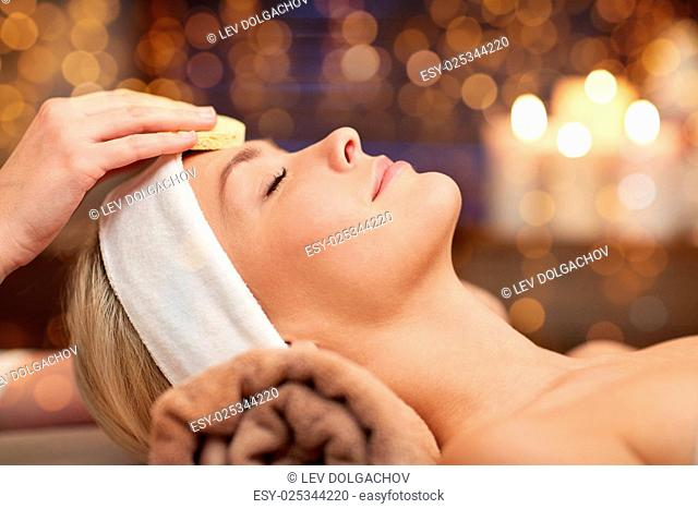 people, beauty, spa, cosmetology and relaxation concept - close up of beautiful young woman lying with closed eyes having face cleaning by sponge in spa