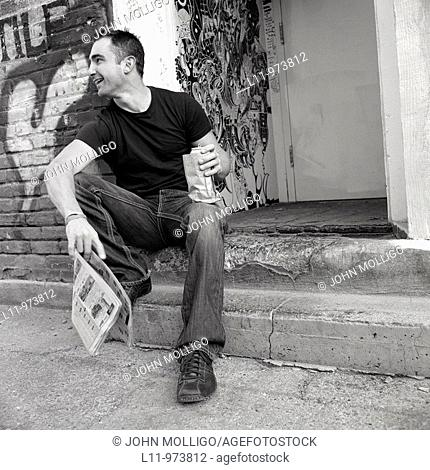 Man seated in alley, with newspaper and beer