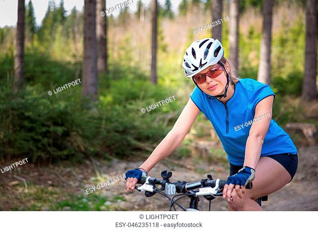Pretty, young female biker outdoors on her mountain bike (shallow DOF; selective focus)