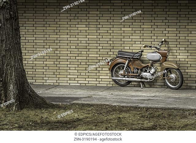 old retro style motor cycle parked in front of a brick wall, stuttgart, baden-wuerttemberg, germany