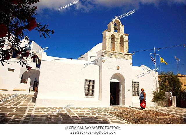 Local woman in front of the Church Of The Holy- Trinity, today the Ecclesiastical Museum of Milos, Adamas, Milos, Cyclades Islands, Greek Islands, Greece