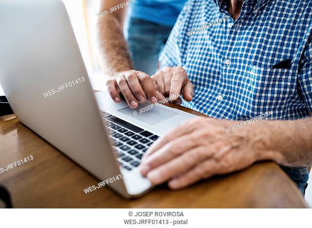 Adult grandson teaching his grandfather to use laptop, close-up
