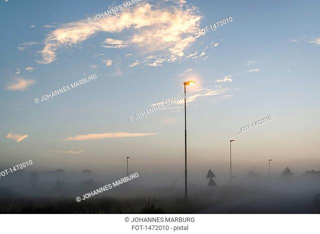 Illuminated street lights in foggy weather during sunset
