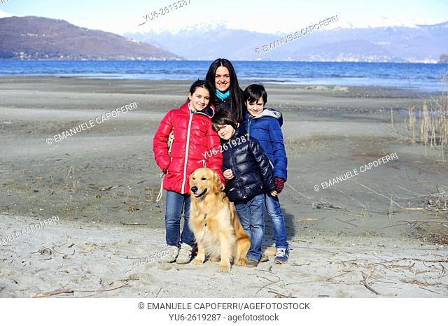 Mom with her three children and a dog on the beach of Lake Maggiore, Ispra, Italy