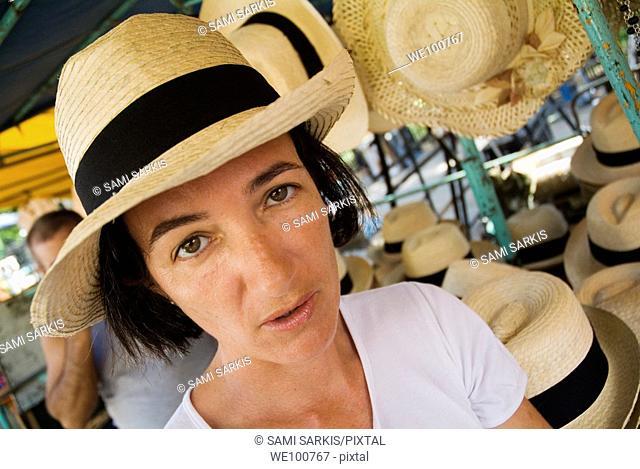 Woman wearing a straw hat bought at the market, Havana, Cuba