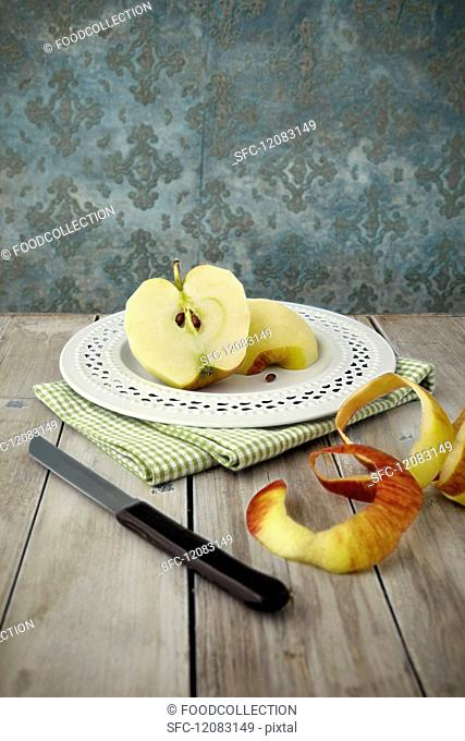 A peeled apple cut in half on a plate
