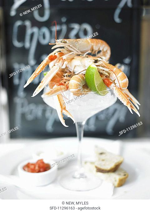 Whole scampi on ice in a cocktail glass served with lime, dips and white bread