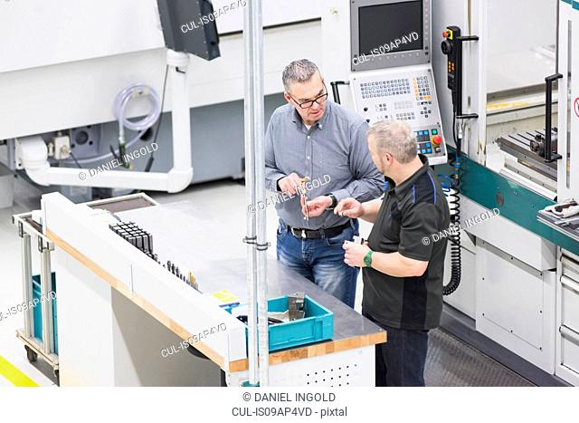 Factory workers having discussion in factory workstation