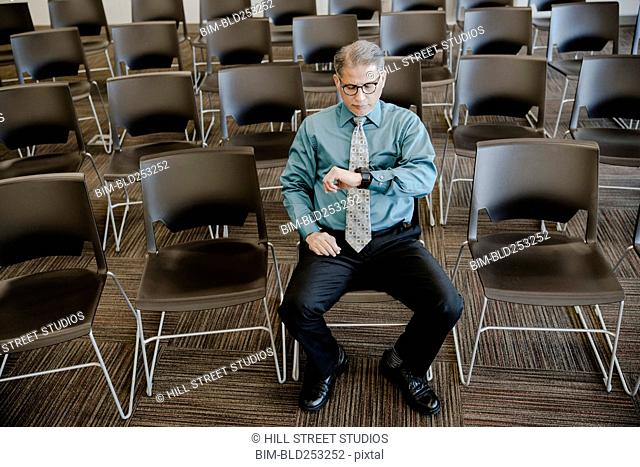 Hispanic businessman checking wristwatch in conference room