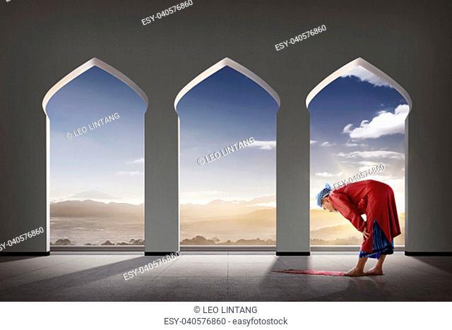 Elderly asian muslim man praying inside the mosque