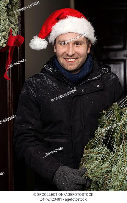 man holding christmas tree with cap