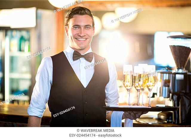 Portrait of waiter holding serving tray with champagne flutes?á