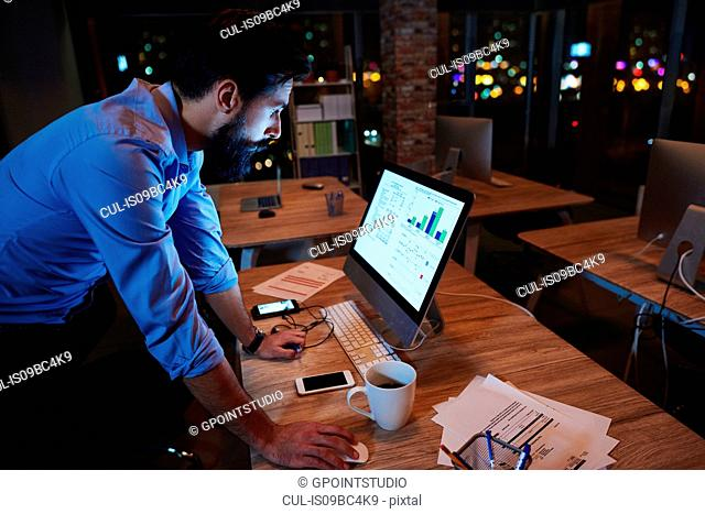 Young businessman working at computer on office desk at night